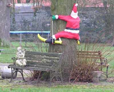 kerstman klimt tegen een boom op